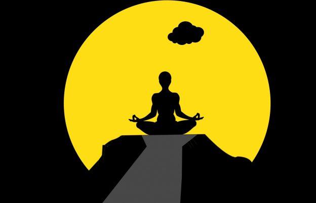 Meditator op een berg bij zonsopgang